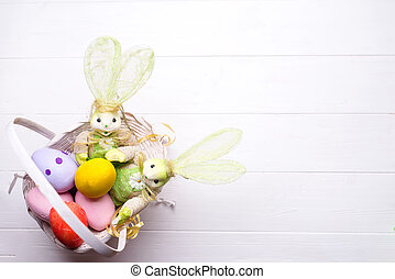 Colorful painted easter eggs in brown basket with rabbits on...