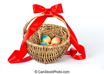 Colorful painted easter eggs in brown basket with red ribbon...