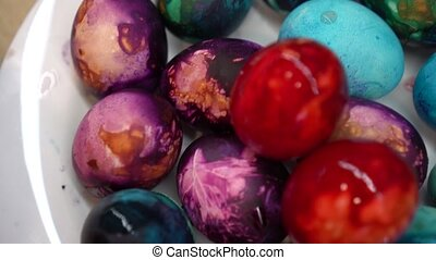 Colorful painted Easter eggs in white dish. Gimbal motion...