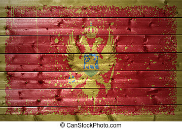 painted montenegrin flag on a wooden texture - colorful...
