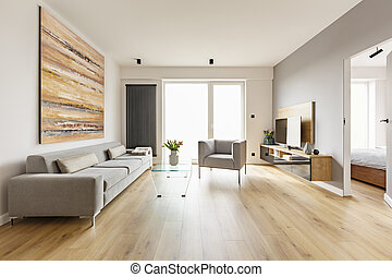 Colorful painting above sofa in living room interior with armcha
