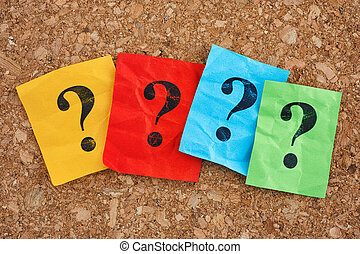 Colorful paper notes with question marks on a cork board