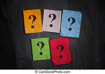 Colorful paper notes with question marks on black board