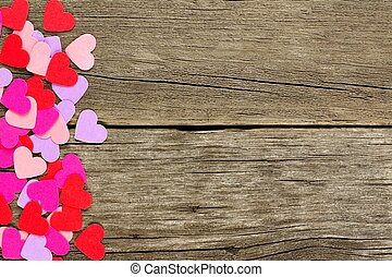 Colorful paper Valentines Day hearts forming a side border against rustic wood