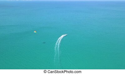Colorful parasail flying over blue sea pulled boat aerial view. Parasailing over blue sea drone view. Summer activity and extreme entertainment while resting on resort beach.
