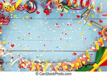 Colorful party streamer and bow tie border on a rustic blue...