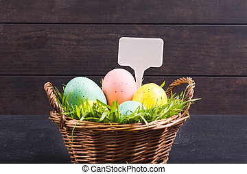 Colorful pastel Easter eggs with green natural grass in basket with white label. Copy space