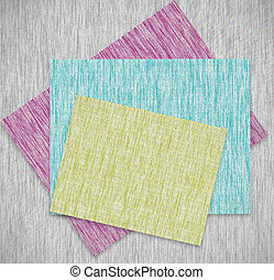 Colorful patches of fabric stacked on a pile of paper