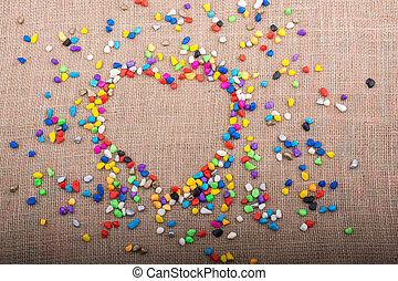 Colorful pebbles form a heart shape on canvas ground