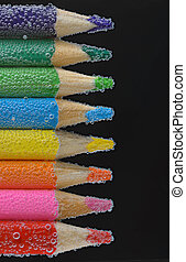Colorful pencils close-up into water