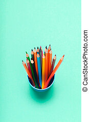 Colorful pencils in a cup on blue background top view
