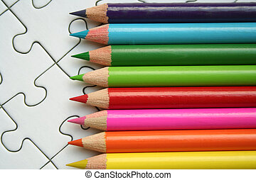 Colorful pencils on jigsaws background