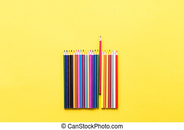 Colorful pencils on the yellow background