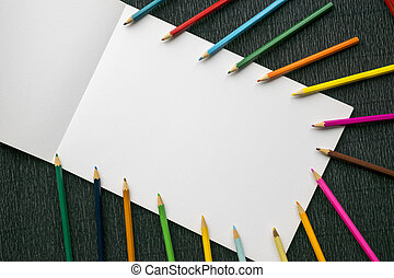 Colorful pencils on white paper copy space over wooden textured background.