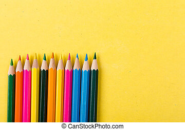 Colorful pencils on yellow background.