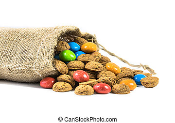 Colorful pepernoten treats in jute bag on white background