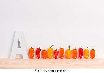 Colorful peppers and letter A on wooden surface