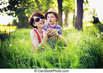 Colorful photo of mother and kid playing blow-balls - ...