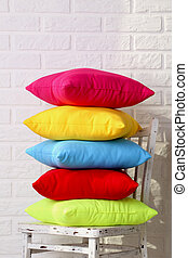 Colorful pillows on chair on white brick wall background