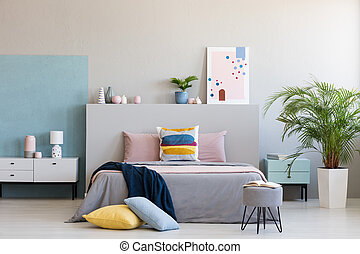 Colorful pillows on grey bed in modern bedroom interior with poster and plants. Real photo
