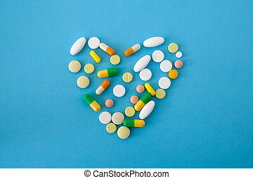 colorful pills and capsules in shape of heart
