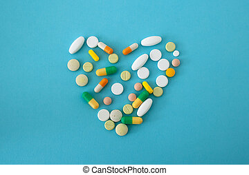 colorful pills and capsules in the shape of heart