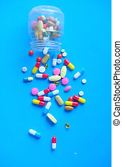 colorful pills spilling on blue background, top view