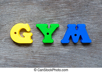 Colorful plastic alphabet in word GYM on wood background