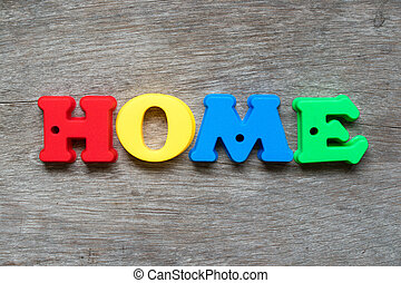 Colorful plastic alphabet in word home on wood background
