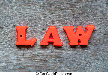Colorful plastic alphabet in word law on wood background
