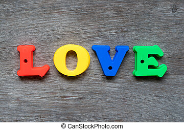 Colorful plastic alphabet in word love on wood background