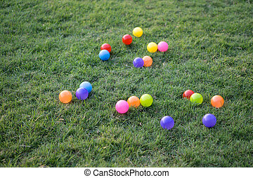 colorful plastic balls on green grass