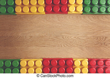 Colorful plastic construction blocks on wooden background as frame. Flat lay. Top view