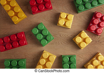 Colorful plastic construction blocks on wooden background. Flat lay. Top view