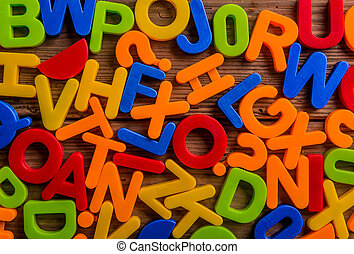 Colorful plastic letters and numbers laid on wooden ...
