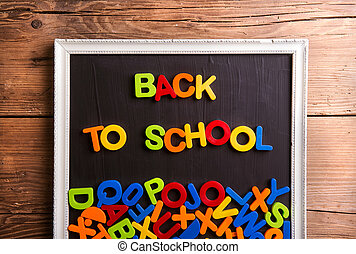 Colorful plastic letters in picture frame, back to school