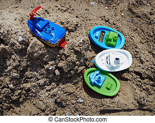 Colorful plastic toy floating boats on the sand beach by the ocean sea ready for fun play time