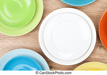 Colorful plates and saucers over wooden table background. ...