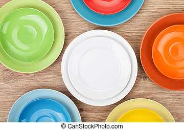 Colorful plates and saucers over wooden table background....