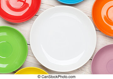 Colorful plates over wooden table background