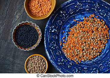 Colorful plates with assorted lentil on a dark background