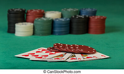 Colorful poker chips with cards on green background