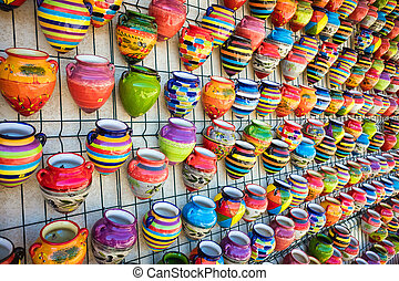 Colorful pots of pottery hanging at wall