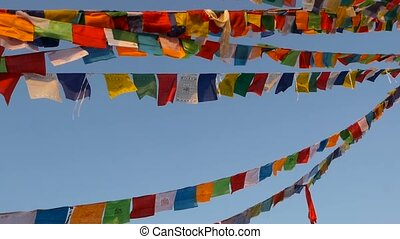 Colorful prayer flags flying in the wind at Boudhanath Stupa, Holy Pagoda, symbol of Nepal and Kathmandu with golgen Buddha's Eyes. Sunset ligth