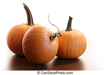 Colorful pumpkins on wood table against white