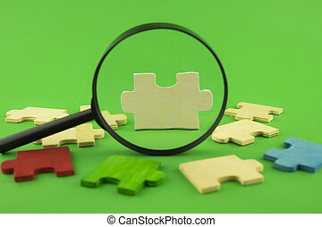 Colorful puzzle pieces with magnifying glass