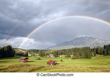 colorful rainbow over alpine meadows with wooden huts