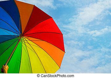 colorful rainbow umbrella on blue sky background