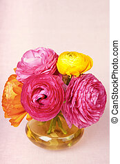 Colorful ranunculus flower in a yellow vase on vintage background