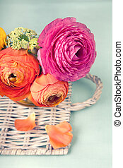 Colorful ranunculus flower on a wicker tray